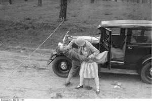 Wie schützt sich die alleinfahrende Auto-Fahrerin vor einem Ueberfall! Durch Jiu-Jitsu, einer einfachen Verteidigungsmethode ist jeder Mensch in der Lage, sich bei einem Überfall tatkräftig zu wehren und den Verbrecher sogar unschädlich zu machen. Ein Beispiel. Der Verbrecher hat ein Seil quer über die Landstrasse gespannt und das Auto zum Stehen gebracht, um die Autofahrerin zu berauben. Der Angriff des Verbrechers wird durch einen wirksamen Jiu-Jitsu-Griff an die Kehle abgewehrt.